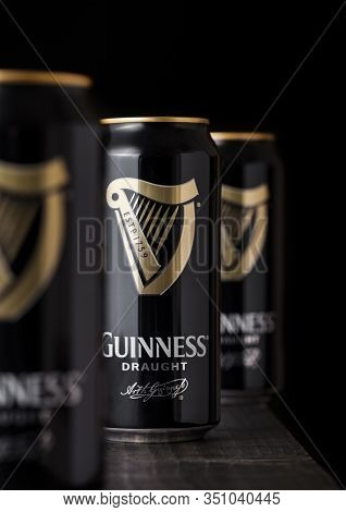 London, Uk - April 27, 2018: Aluminium Cans Of Guinness Draught Stout Beer Bottle On Dark Wooden Bac
