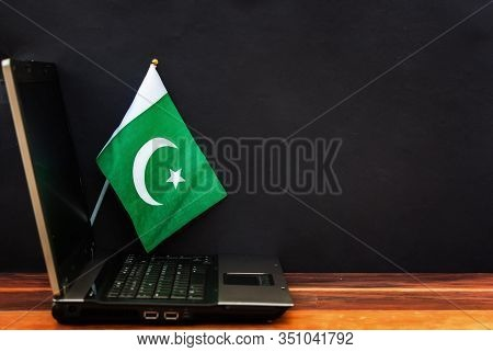 Flag Of Pakistan , Computer, Laptop On Table And Dark Background