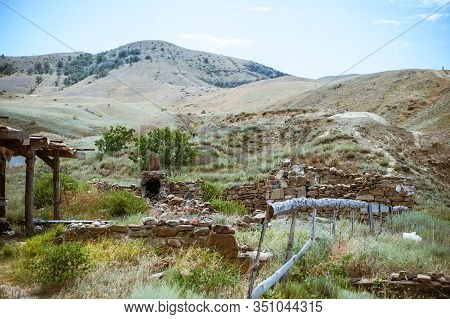 Old Ruined Log House And Stone Stove In The Yard In Crimean Steppe On A Background Of Mountains