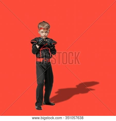 Full Lenght Portrait Of Young Boy In Kimono Posing In Karate Position On Red Background