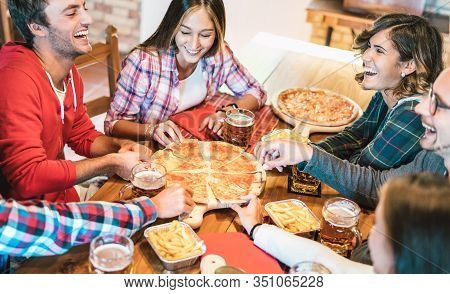 Young Friends On Genuine Laugh While Eating Pizza At Home On Family Reunion - Friendship Concept Wit