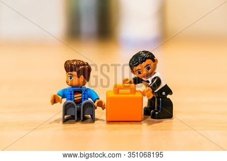 Poznan, Poland - February 16, 2020: Lego Duplo Thief Trying To Steal A Orange Suitcase From A Sittin