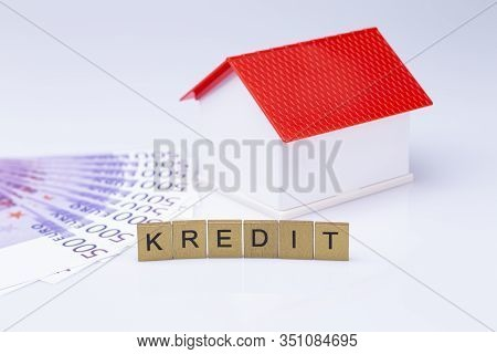 The Photo Shows A White Model House With Red Roof And Wooden Letters And Cash