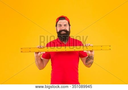 Happy About Size. Bearded Man With Big Measuring Instrument. Measuring His Height With Ruler. Gauge