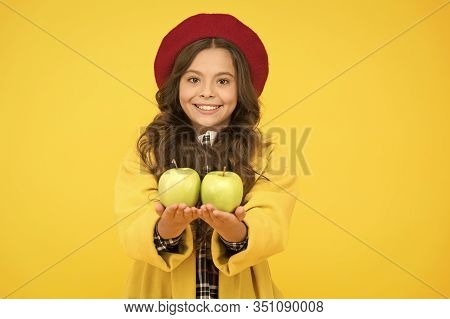 Get Vitamin Start To School Year. Happy Girl Hold Vitamin Fruit Yellow Background. Little Child Smil