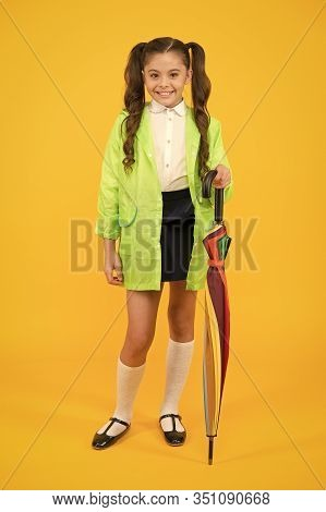 Cute And Practical Style. Happy Small Girl Holding Umbrella Cane With Elegant Style On Yellow Backgr