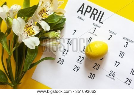April 2020 Monthly Calendar With Yellow Easter Egg On The Bright Yellow Background. Close-up View Of