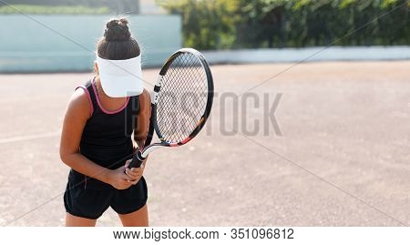 Portrait Of Young Teenage Girl, With Racquet In Hand On Tennis Court, Waiting For Serve. Wearing Bla