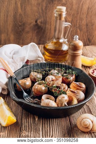 Bourgogne Escargot Snails With Herbs Butter In Iron Pan On Rustic Wooden Background. Selective Focus