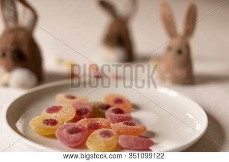Three Brown Felt Bunnies Waiting For Jellybeans Candies In A White Plate In Foreground. Bunnies Out