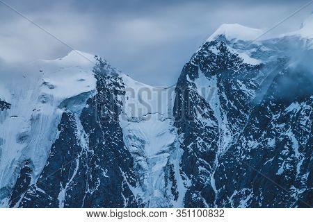 Mysterious Dramatic Alpine Scenery With Snowy Mountain Top Inside Low Clouds In Dusk. Bleak View To