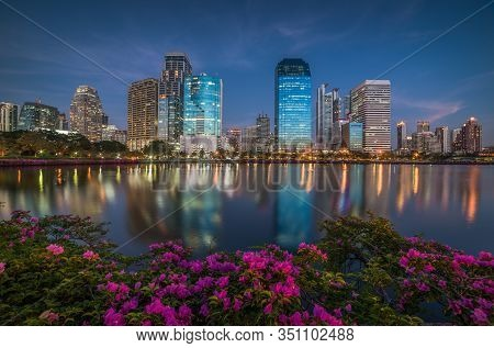 Lake With Purple Flowers In City Park Under Skyscrapers At Twilight. Benjakiti Park In Bangkok, Thai