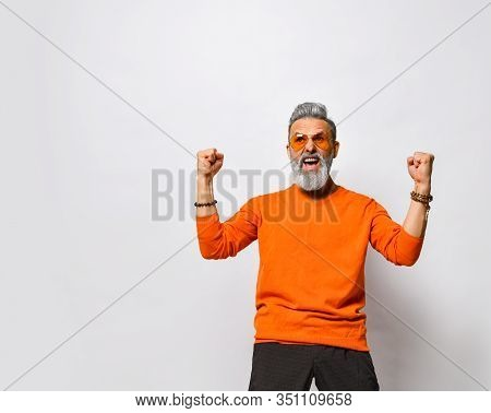 Screaming Older Bearded Man In Orange Sweater And Sunglasses And Looking At The Camera With Hands Up