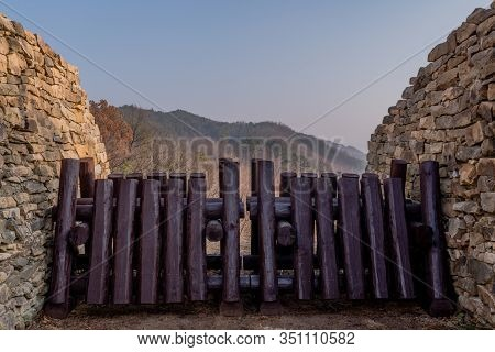Closeup Of Wooden Log Blockade At Gate Of Mountain Fortress Made Of Flat Stones.