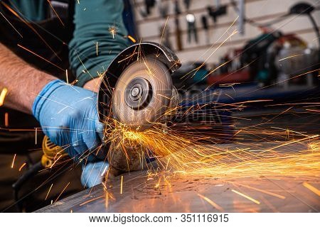A Close-up Of A Car Mechanic Using A Metal Grinder To Cut A Car Silent Block In A Vise In An Auto Re