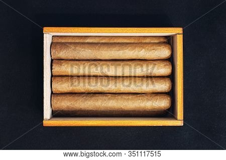 Close Up Of Cigars In Open Humidor Box On Black Table In The Dark.
