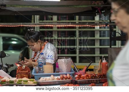 Thailand, Phuket, Patong, February 1, 2020: A Female Street Food Vendor Looks At Her Phone. Night St