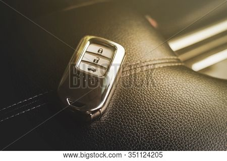 Keyless Remote Of Luxury Car On Leather Armrest In Car.