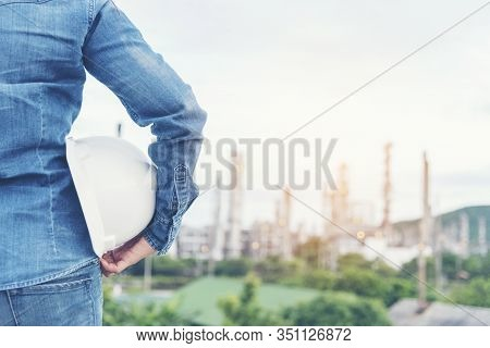 Smart Woman Engineer Holding White Hard Hat On Hand And Look At Refinery Industry Plant At Industry