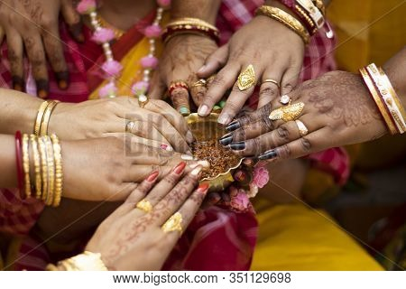 Indian Bride And Women Hands Holding Brass Bowl Of Turmeric