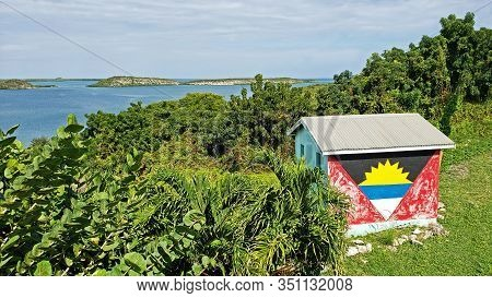 Seatons, Antigua And Barbuda, December 27, 2019:  Shed Painted With The Antigua Flag Overlooking Mer