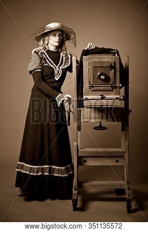Vintage Retro Style Photo Of A Young Woman In A Long Modest Dress And Hat Standing Near A Daguerreot