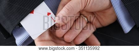 Close-up Of Cheater Hands Pulling Ace Card Out Of Sleeve With Crossed Arms Behind. Gamer With Strong