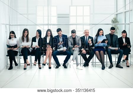Group Of Business People Use Their Gadgets Before Starting A Business Meeting