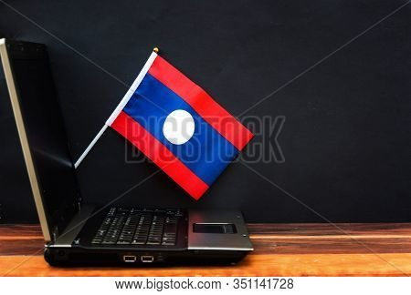 Flag Of Laos , Computer, Laptop On Table And Dark Background