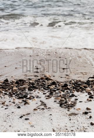 Different Texture On The Beach - Water And Sand, Stones And Pebbles, Waves And Splashes. Selective F