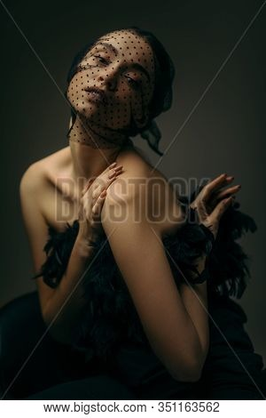 Fashion Portrait Of Beauty Elegant Girl Posing In Black Veil On Dark Background. Gorgeous Stylish Mo