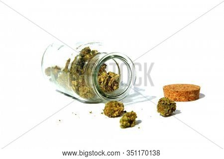 Marijuana. Cannabis Sativa or Cannabis Indica in a Glass Stash Jar with a cork lid. Isolated on white. Room for text. Clipping Path. Marijuana is enjoyed world wide and legal in many area of the world