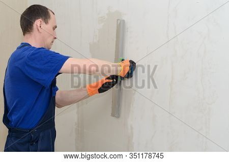 Uniform Worker Plastering A Room Wall With Gypsum Plaster