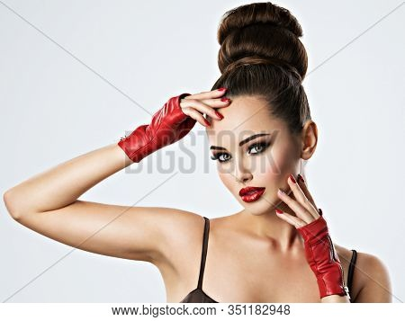 Beautiful sensual woman with glamour makeup. Fashion model with stylish creative hairstyle. Pretty sensual young adult girl in red leather gloves