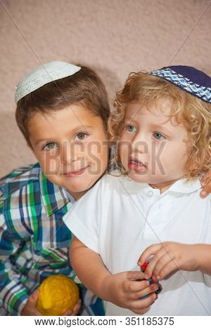 Two beautiful Jewish boy in skull-caps. The elder brother holds a ritual fruit - Etrog. Sukkot