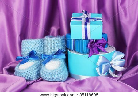 blue baby boots and gifts on silk background