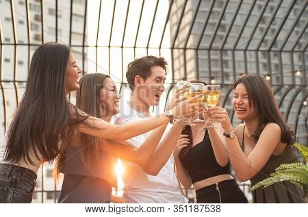 Group Of Asian Multiple Gender Holding Glass Of Wine Chat Together With Friends While Celebrating Da