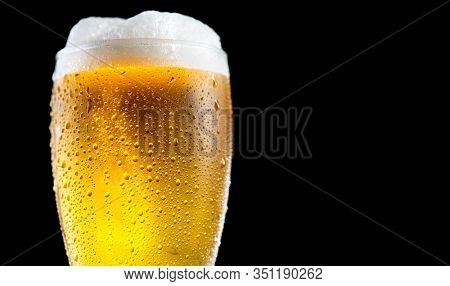 Beer. Cold Craft light Beer in a glass with water drops. Pint of Beer close up isolated on black color background. Ale beer Border design. Closeup
