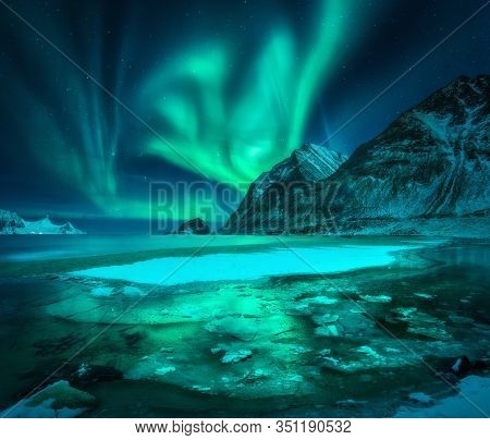 Aurora Borealis Over Snowy Mountains, Frozen Sea Coast And Reflection In Water In Lofoten Islands, N