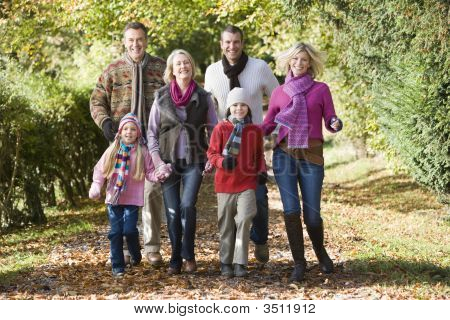 Family Walking Outdoors In Park Smiling