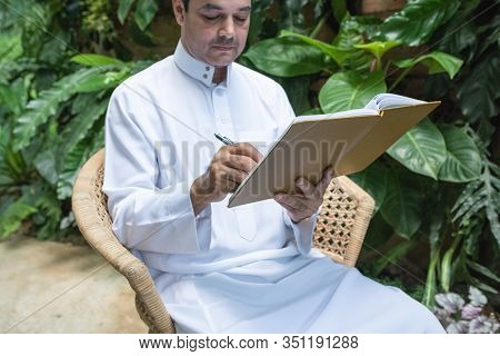 Saudi Muslim Man Dress Hijab Sitting And Writing On Textbook,freelance Business Concept.