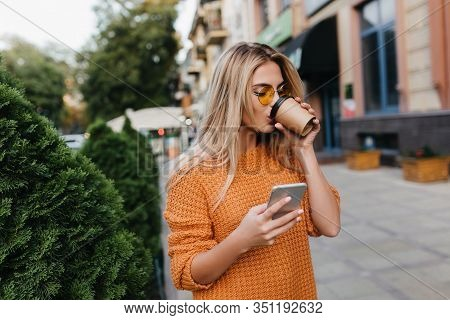 Enchanting Blonde Young Woman Waiting For Phone Message While Drinking Coffee On The Street. Stylish