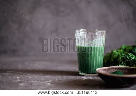 A Glass Of Healthy Vegan Drink Green Kale Smoothie With Spirulina For Detox On Dark Background Close