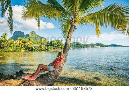 Tropical travel nature background tourist woman on eco tourism destination relaxing lying down on palm tree tropical landscape. Bora Bora island with Otemanu mountain view, Tahiti, French Polynesia.