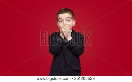 Astonished Kid In School Jacket Covering Mouth And Looking At Camera After Learning Secret Against R