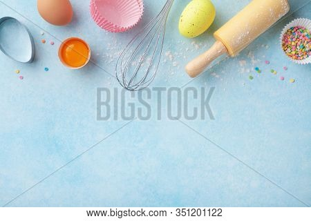 Easter Baking Background With Rolling Pin, Whisk, Eggs, Flour And Colorful Confetti On Blue Table To
