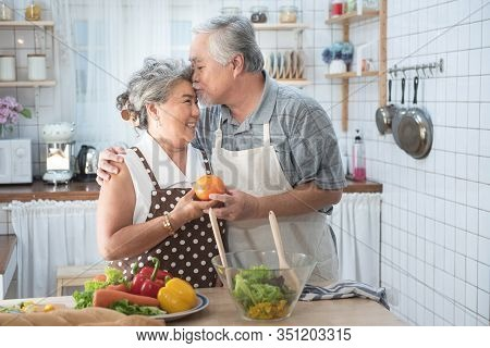 Senior Couple Having Fun In Kitchen With Healthy Food - Retired People Cooking Meal At Home With Man