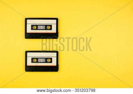 Retro Audio Cassette Tape Flat Lay On Colorful Yellow Background Top View With Copy Space. Creative