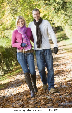 Couple Outdoors Walking On Path In Park Smiling