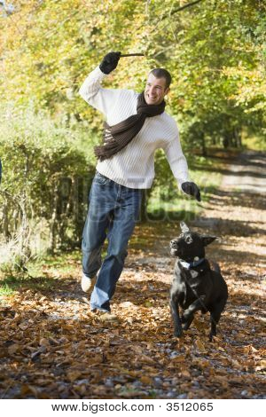 Man throwing stick for dog in woodland smiling poster